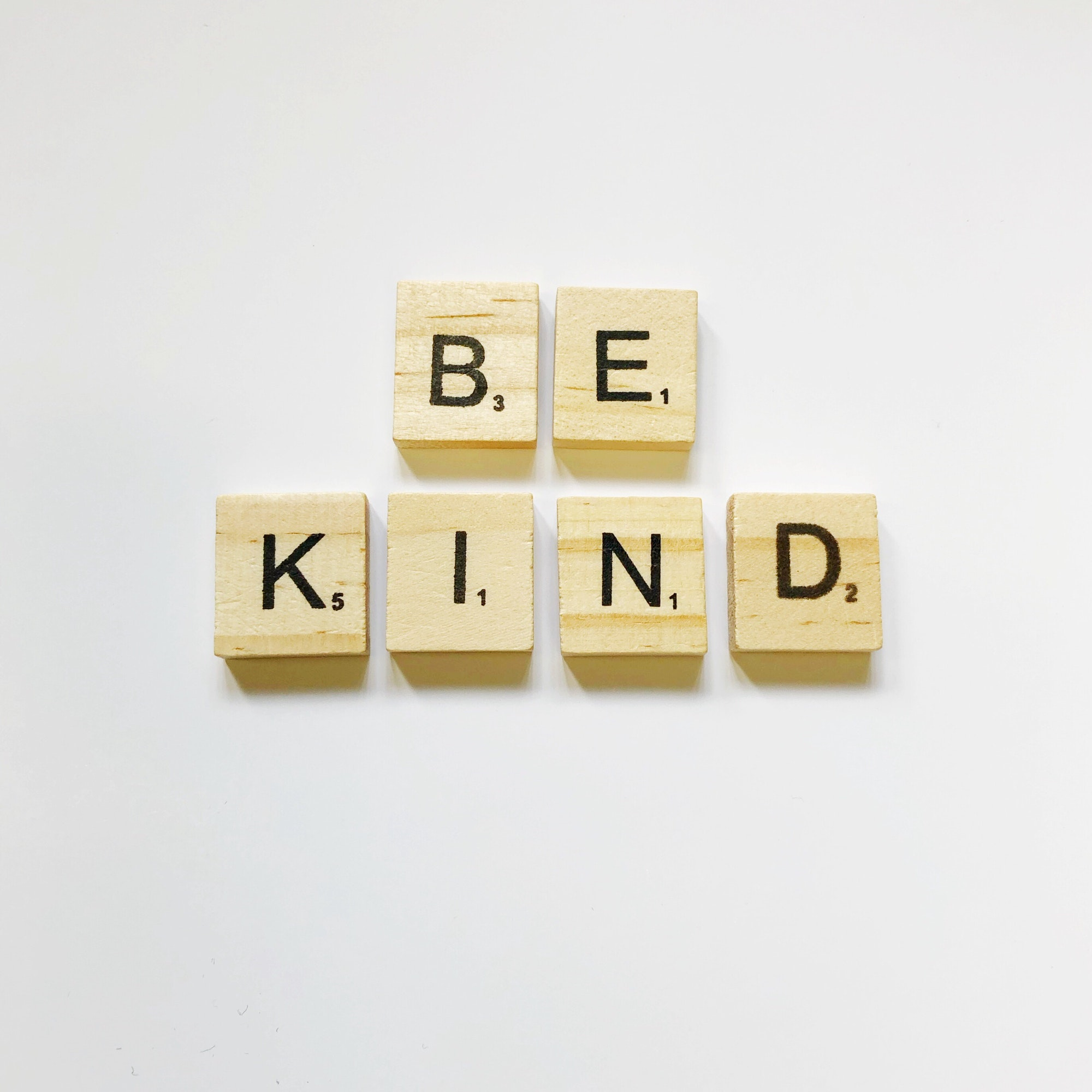 Be kind in wooden letters on a white background